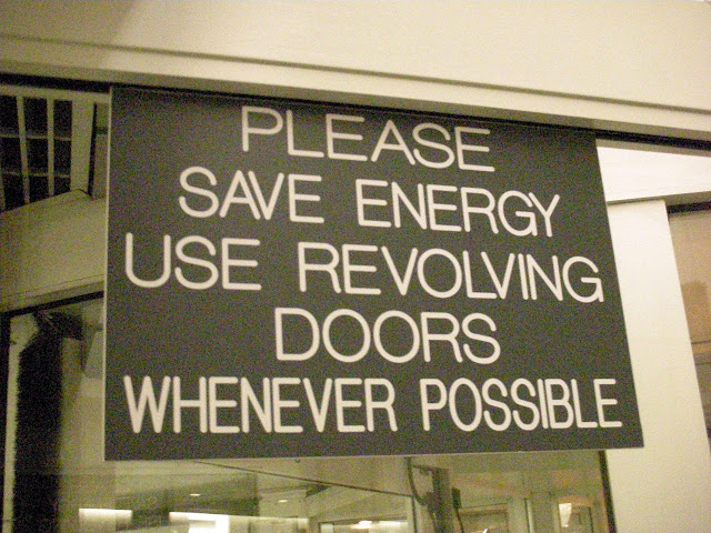 Signs encouraging the usage of revolving doors at a building in Syracuse, New York.