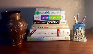 Photo of a stack of language books and dictionaries.  A brass vase to one side and a Paris themed pencil holder to the other.