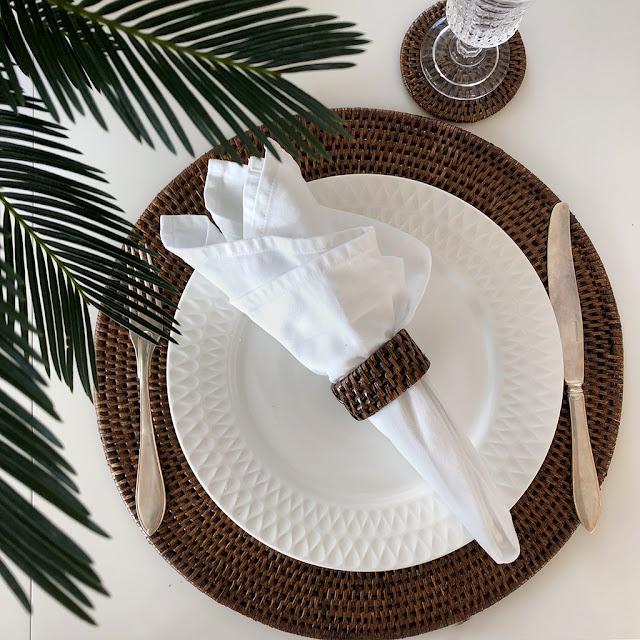 Rund bordstablett i brun rotting från Baolgi hos återförsäljare Longcoast Living. Kolonial inredning stil med brun rotting.