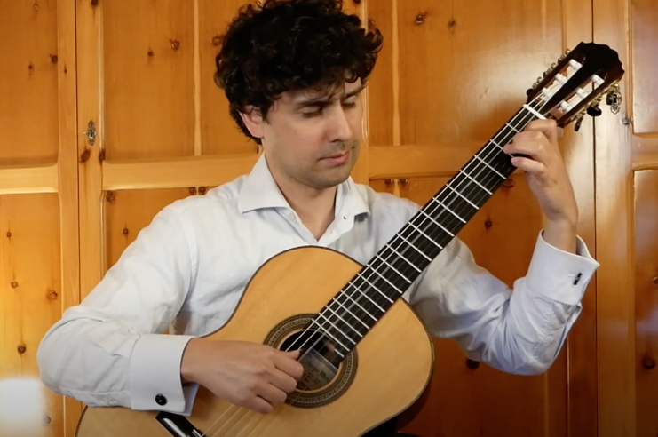 Esdras Maddalon de olhos fechados tocando guitarra clássica.