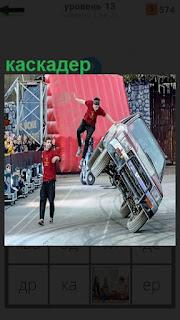 Каскадер выполняет трюк стоя на машине, которая едет на двух колесах