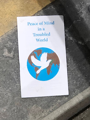 "Front cover of pamphlet showing the Earth with a white dove over it, the title above reads, ""Peace of Mind in a Troubled World."""