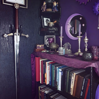 A two-handed claymore sword is mounted on an ornate metal two-pronged mount screwed into a wall clad with black reptile-skin effect wallpaper. The image is looking into a corner. The wall on the right is a dark purple and is stencilled with silver and gold stars. There are three moon-design mirrors in a folk style from Indonesia on the wall, in varying shades of purple with black and gold accents. In the corner there is a three-tier black-painted glossy shelf with various witchy items on it including two resin figures of wizards, several ornate boxes and a statue of Bast. There is a book-case standing from the floor; it is gloss black, and it has a berry purple altar-cloth along the top of it. There is a Neo-Pagan altar set up with a black cast-iron cauldron, an incense censer in the shape of the Moon Goddess, a glass crescent moon candle-holder, several crystals, even more purple glass candle-holders, and a purple incense burner for joss sticks. There are two rolled beeswax candles, purple. The lighting is daylight, the image is relatively bright considering the dark space. Sunlight glints on the faux-reptile wallpaper. There are books on the book-case, disorganised and mis-matched, they are about architecture and include modern books and 19thC volumes