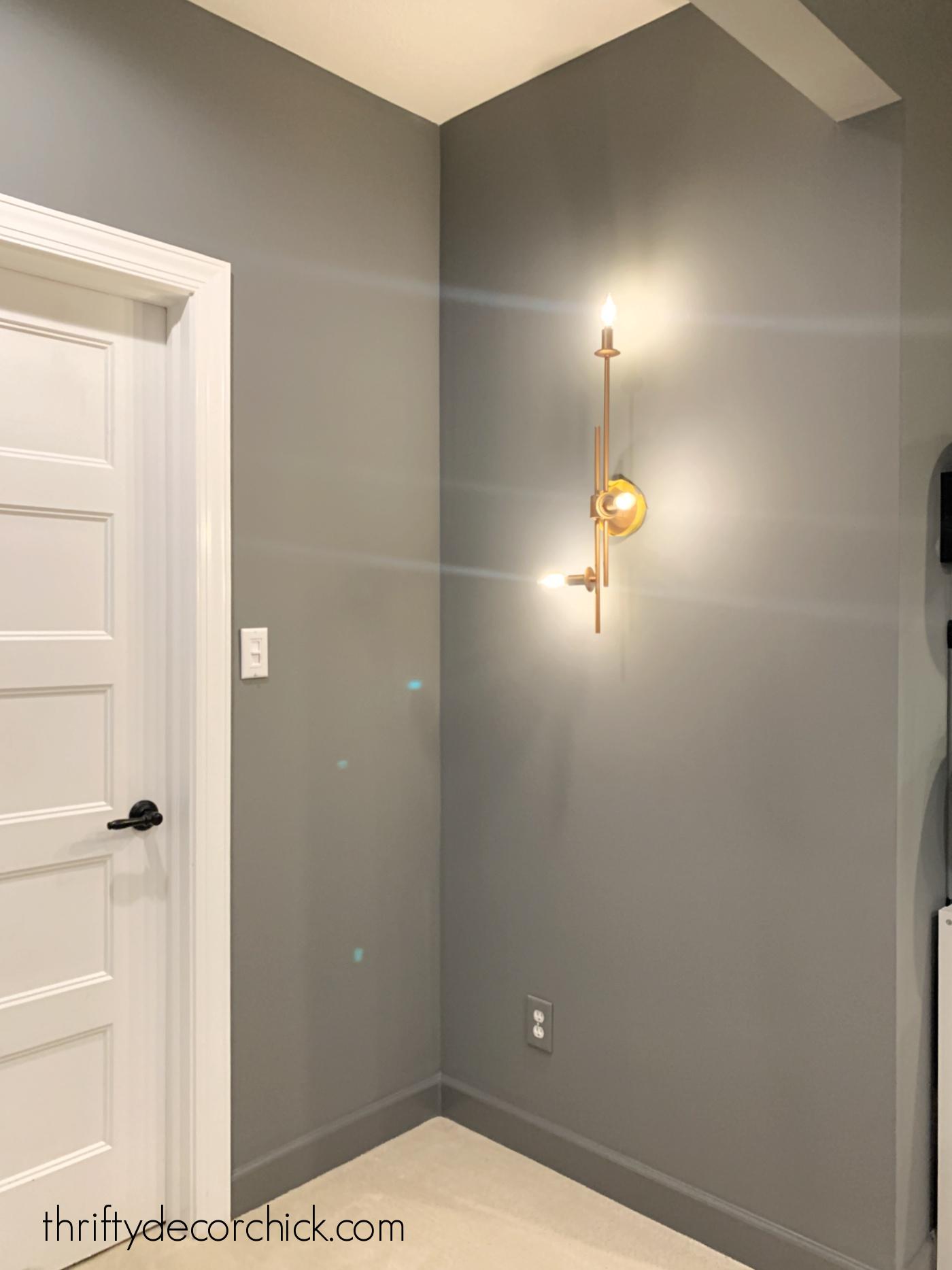 dark gray walls with brass light fixture