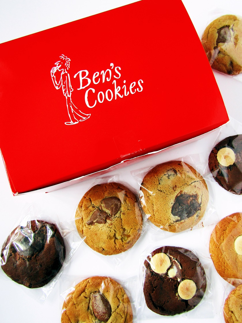 A flatlay photo looking down at a red box of Ben's Cookies, with a selection of fresh chocolate chip cookies in cellophane in front of it.