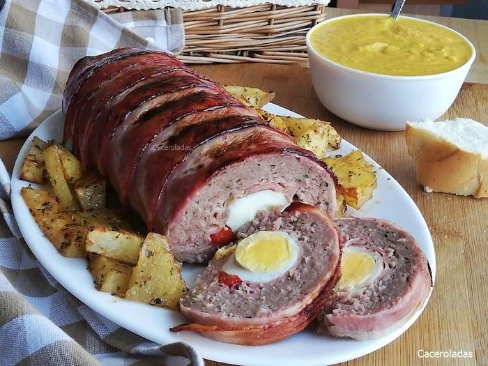 Rollo de carne picada relleno, acompañado de salsa y patatas