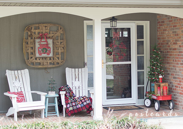 front porch decorated for Christmas with red wagon, white chairs, and various decor