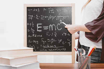 Chalkboard with equations and teacher