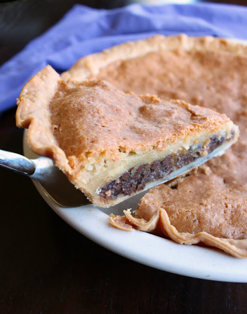 lifting slice of pie with chocolate layer, gooey layer and crackly topping out of pie