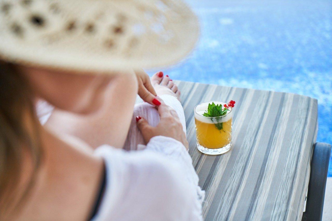 silhueta de mulher na beira da piscina com uma caipirinha de maracuja na bancada