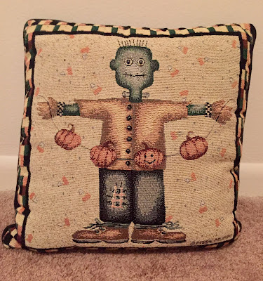 picture of a pillow designed by Debbie Mumm, an image of Frankenstein, pumpkins, and candy corn are sewn on it