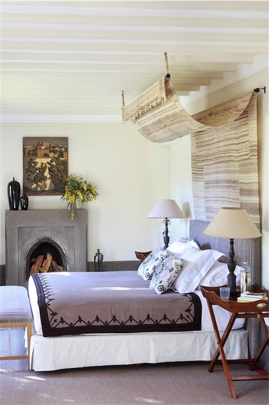 dormitorio con cama con dosel y chimenea casa en Marrakech chicanddeco