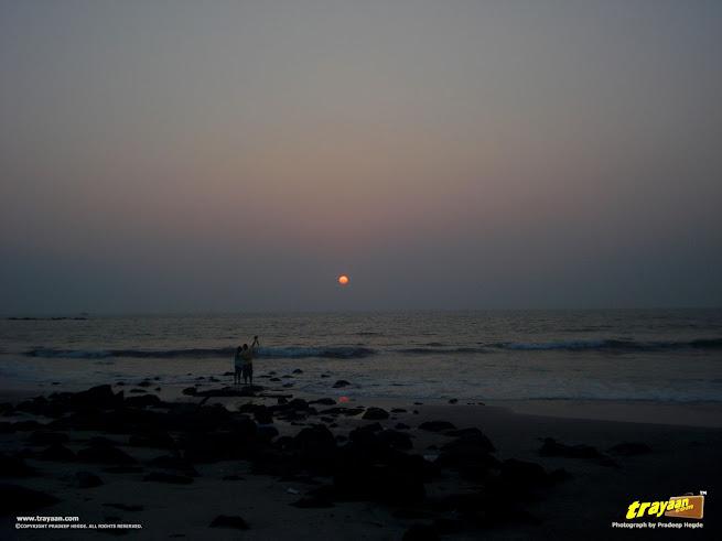 A couple, photographing the sunset at Tannirbavi Beach, Mangalore, Dakshina Kannada, Karnataka, India