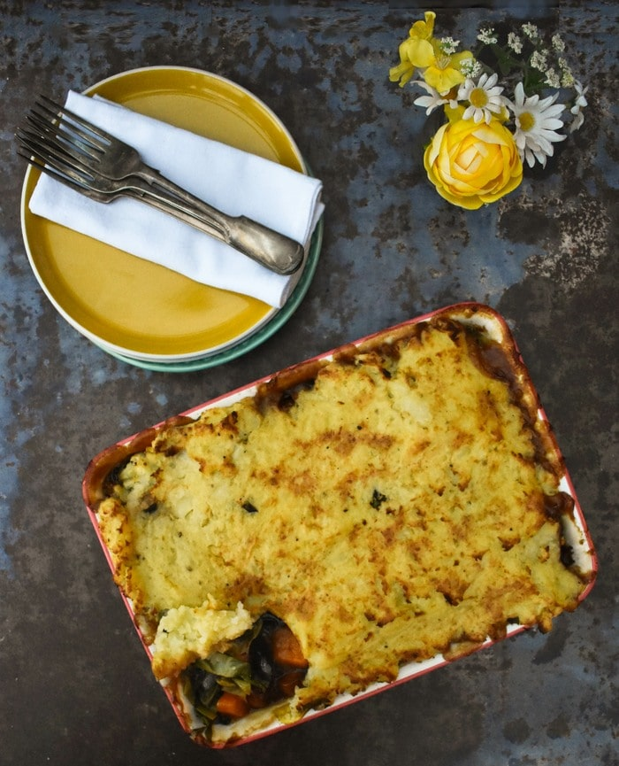 squash and leek sausage pie from above next to yellow plates and yellow flowers