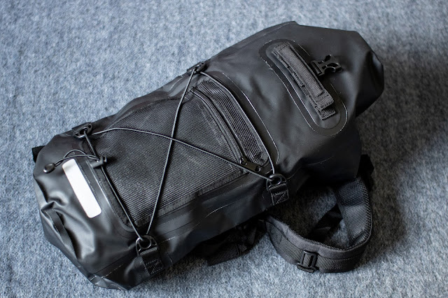 The front of a waterproof backpack in black with a reflective strip