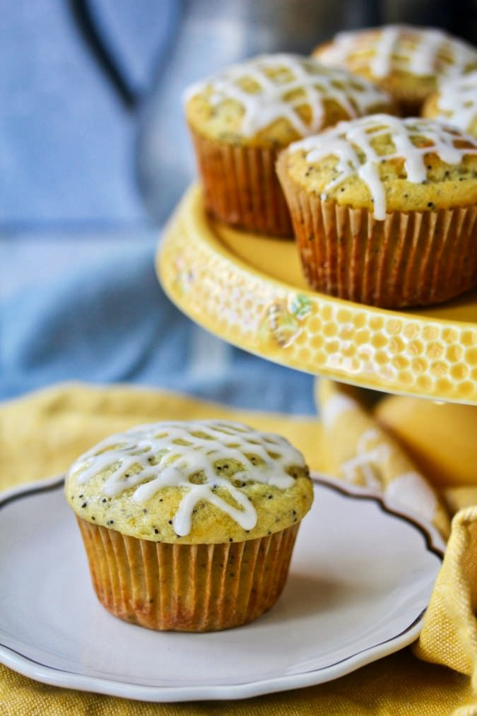 Lemon Poppyseed Ricotta Muffins on a plate. These muffins are so moist, tangy, sweet, and fluffy.
