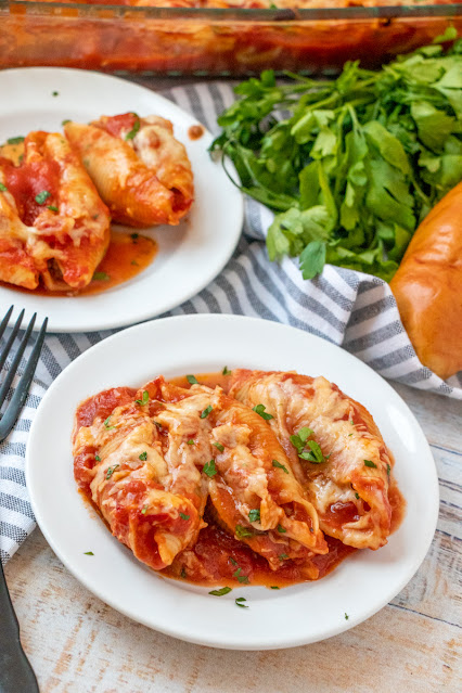 stuffed shells on a plate with linen in the background.