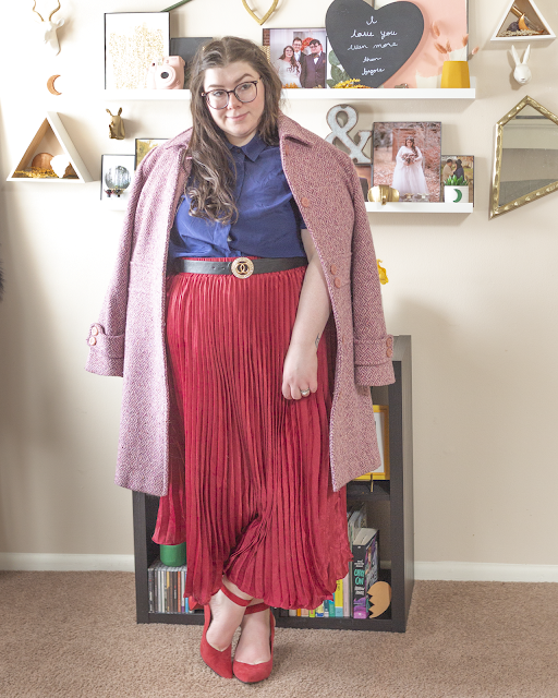 An outfit consisting of a pink marled coat draped over the shoulders of a navy blue button down blouse tucked into a wine pleated maxi skirt and red ankle strap heels.