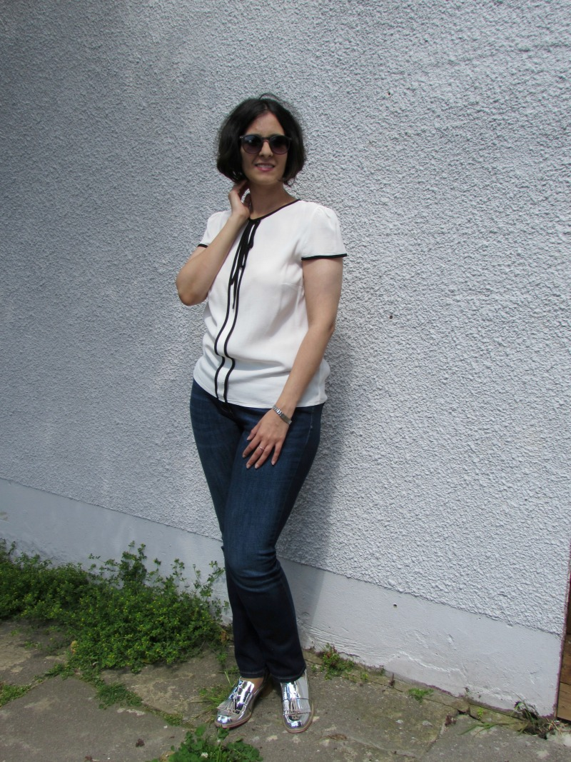 white top, blue jeans and metallic loafers