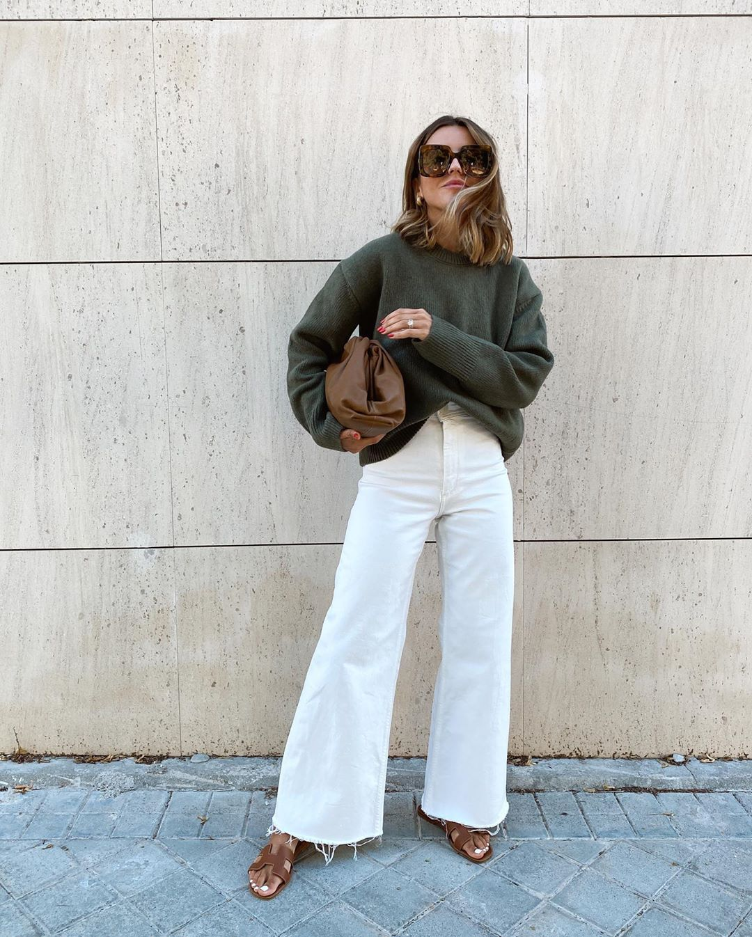 How to Wear White jeans for Fall — Alexandra Pereira in a green sweater, Herems sandals, and Bottega Veneta bag.