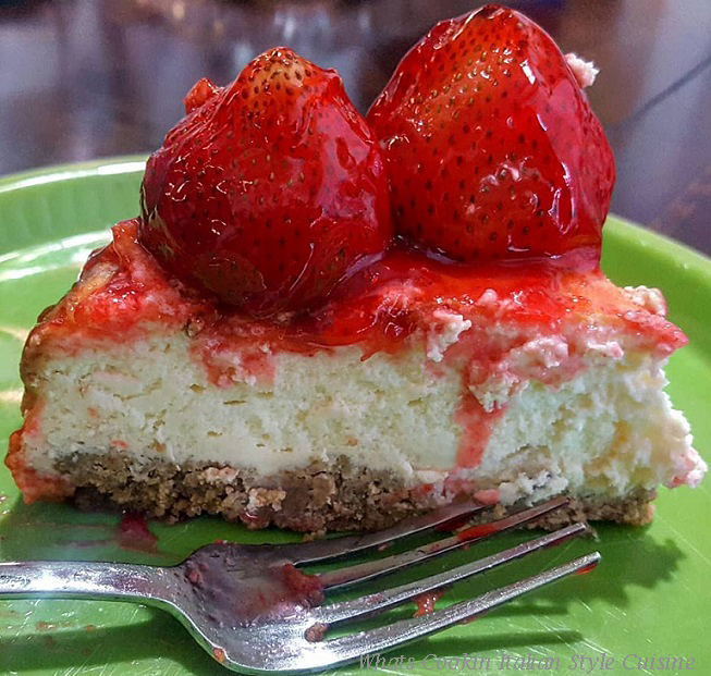This is a knockoff copycat recipe of Manny's cheesecake from Utica, New York from the 1960s. It no longer exsists. This cheesecake is on a green plate and just a slice with whole strawberries on top dipped in a glaze and dripping down the sides. There is also a fork on the plate.