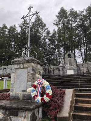 Lower left corner is stone pillar with a metal cross on top. A red, white, and blue wreath has been placed next to the pillar. Behind there are stone steps and a stone wall with plaques honoring 28th Division members who died in World War 1 and World War 2