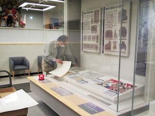 江戸時代のコーナーの展示ケースから、多色摺りの版画など、紙の資料を1点ずつ片付ける学芸員