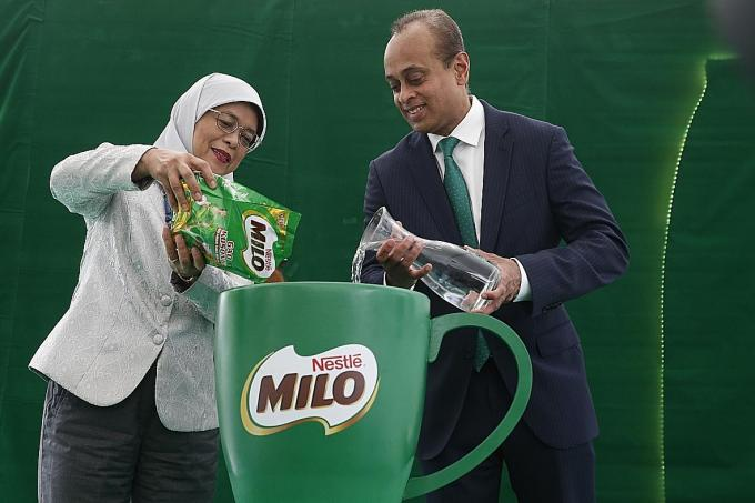President Halimah Yacob helping to make the first cup of Milo Gao Kosong with Nestle Singapore's managing director Rajiv Deraniyagala.