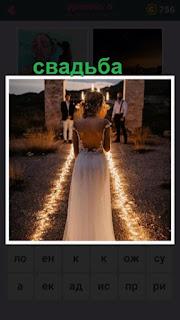 происходит церемония свадьбы на улице с освещением, невеста в платье идет