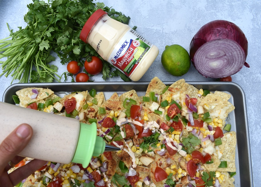 putting Mexican street corn sauce on nachos