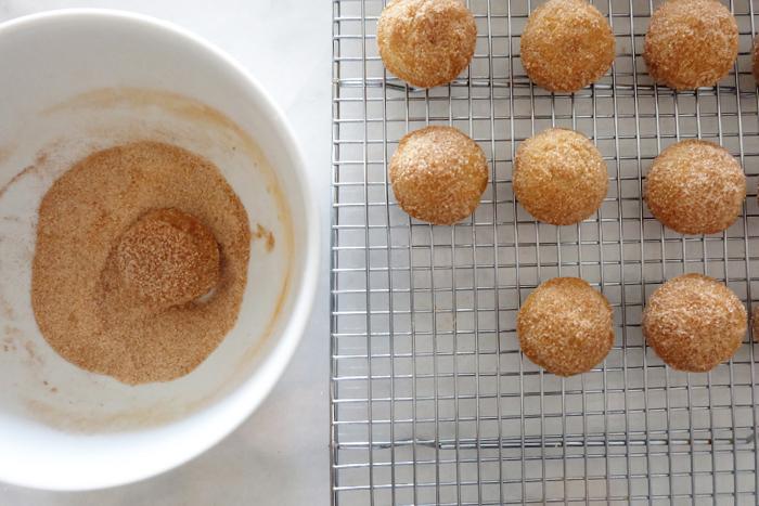 rolling puffs in cinnamon sugar