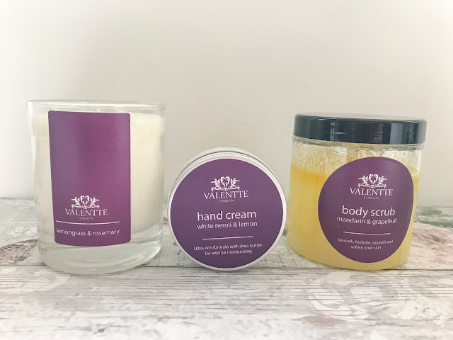 Valentte candle, hand cream and body scrub standing on table