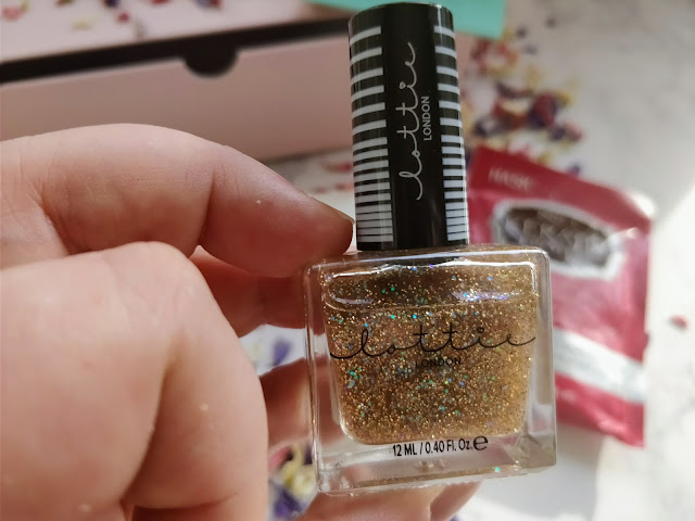Hand holding bottle of Lottie London Lottie Lacquer in hump day, a sparkly nail varnish