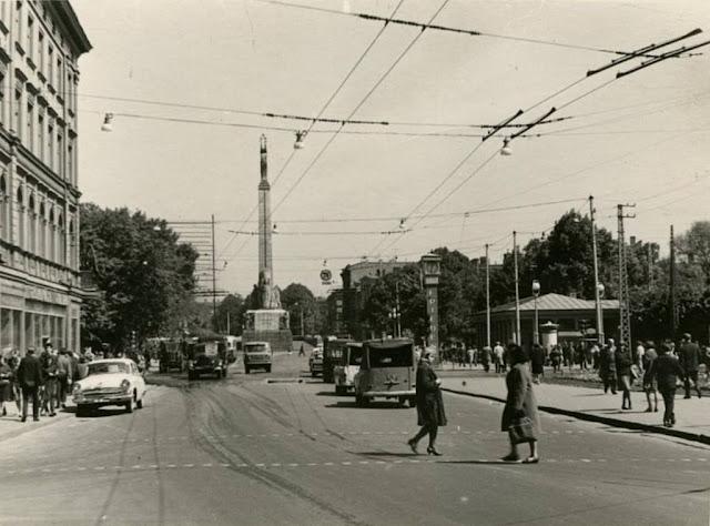 """1960-е годы. Перекресток улицы Ленина и бульвара Падомью. Часы """"Frieden"""", монумент Свободы и нарисованный макет гостиницы """"Латвия"""""""