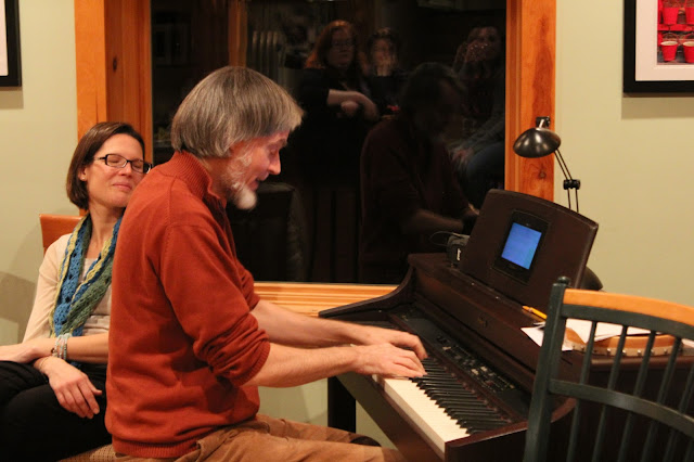David, tenor, previews one of his new compositions at the annual Stairwell Christmas party.