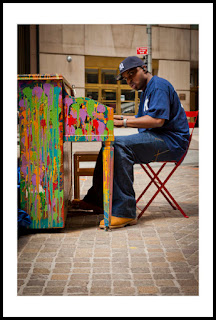 a photo of a man playing a brightly colored painted piano in new york