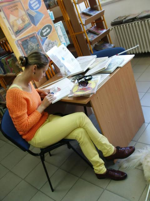 Linda čte text v knize pomocí lupy