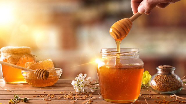 honey in jars being pulled with a honey dipper
