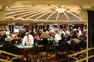 A room in a casino filled with blackjack tables, all busy with players and dealers.