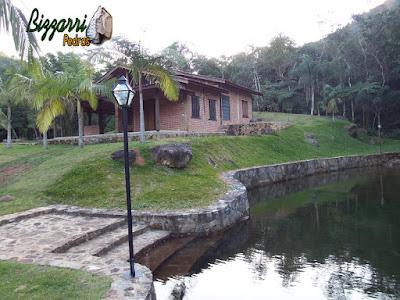 Escada de pedra no lago com os muros de pedra encostado no lago junto a cabana rústica com toras de eucalipto com parede de tijolo a vista sendo essa escada com pedras brutas.