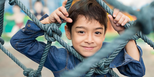Asian American boy climbing on the rope at playground
