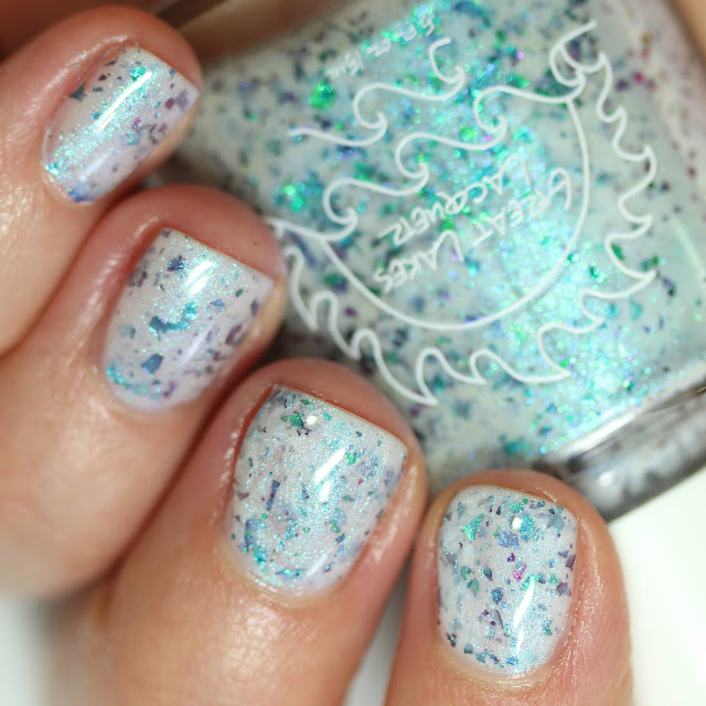 white based nail polish with green to blue to purple shifting multichrome flakes swatched on white person's nails