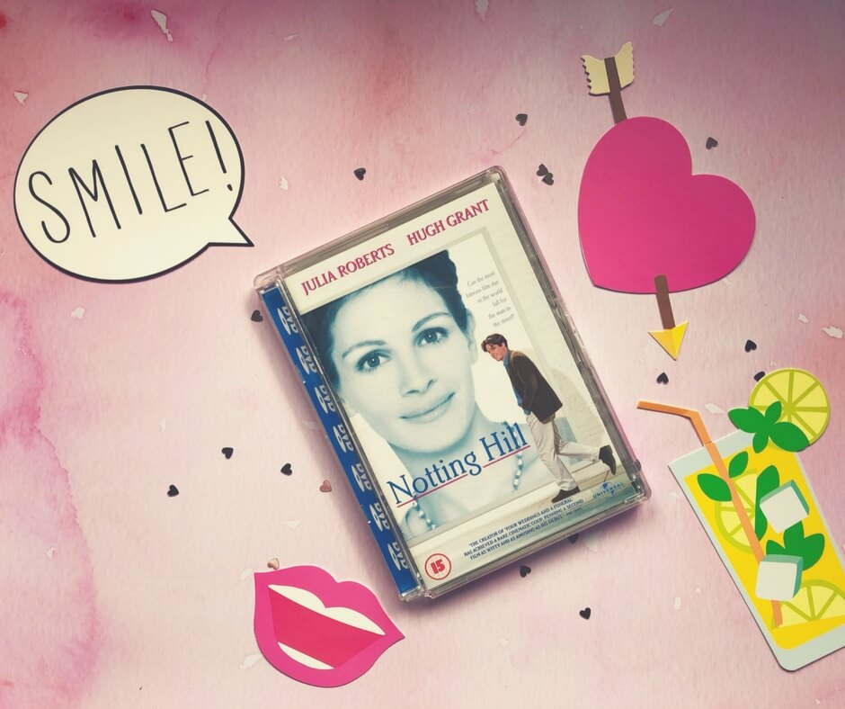 "Notting Hill DVD sits on a pink background surrounded by small silver hearts. In the top right corner is a pink heart with an arrow through it. In the bottom right is a picture of a glass of lemonade. In the bottom left is a smiling mouth with pink lips. In the top left corner is a speech bubble that says ""Smile!"""
