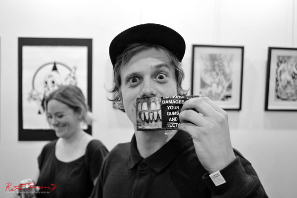 Portrait of a man with cigarette warning photo of bad teeth as a mask. GORO at m2 gallery. Photographed by Kent Johnson for Street Fashion Sydney.