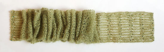 Beaded green hand knit lace scarf on a white background, scrunched up horizontally to better fit in the photo..