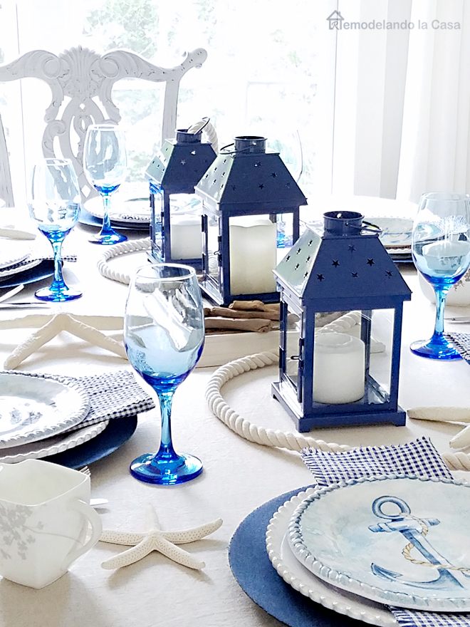 Blue and white table with anchor plates and lanterns centerpiece