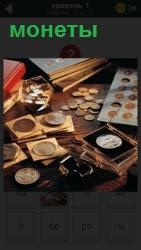 на столе много различных монет лежат в коробках и просто так