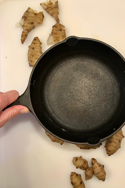 Small skillet smashing boiled sunchokes on a cutting board.