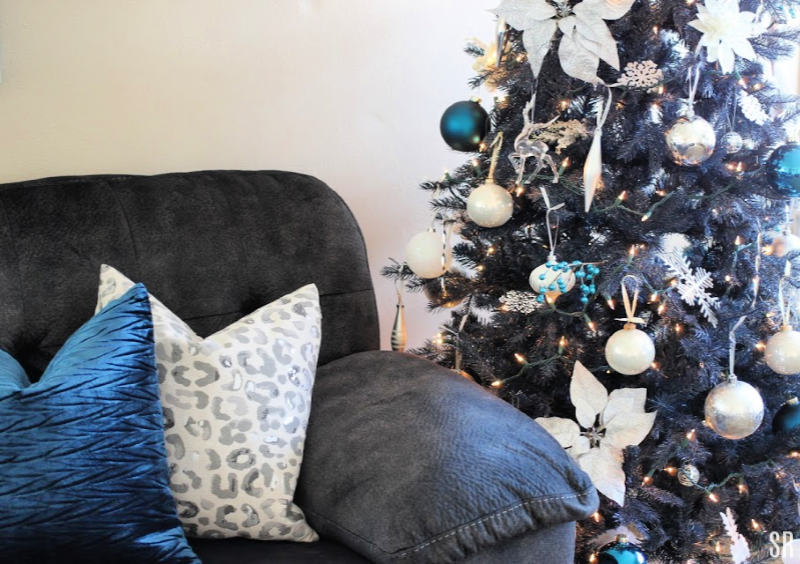 a living room with blue Christmas tree