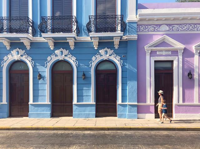 Madre e hijo paseando delante de unas fachadas turquesa y morada en Mérida, Yucatán